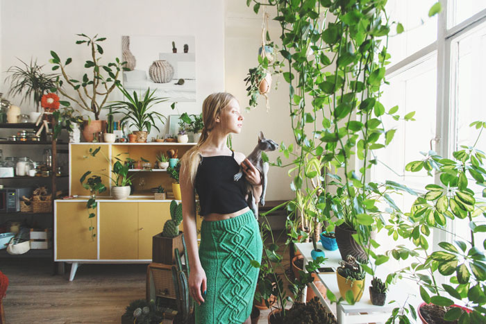 girl gardener with a cat in her arms looking out the window against a background of indoor plants; what does green living really mean?