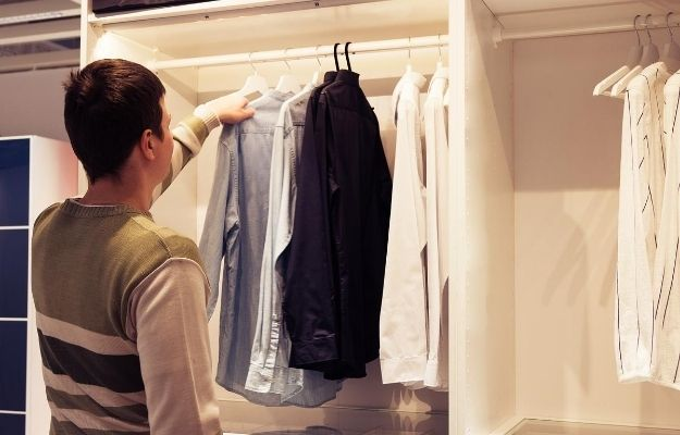 a man is choosing clothes | How To Start A Capsule Wardrobe To Help The Environment