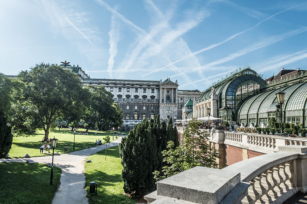A park with green grass and trees visible from a stone balcony. On the right side, a beautiful building at Josefsplatz in Vienna.