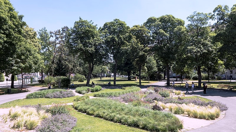 A park with trees, low bushes and flower beds with people strolling around.