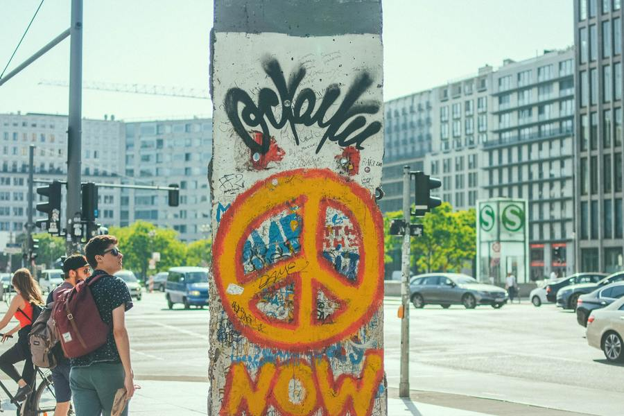 A piece of the Berlin wall with a peace sign painted on it.