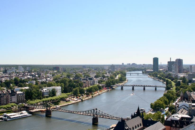 The Main river in Frankfurt with several bridges, buildings and trees.
