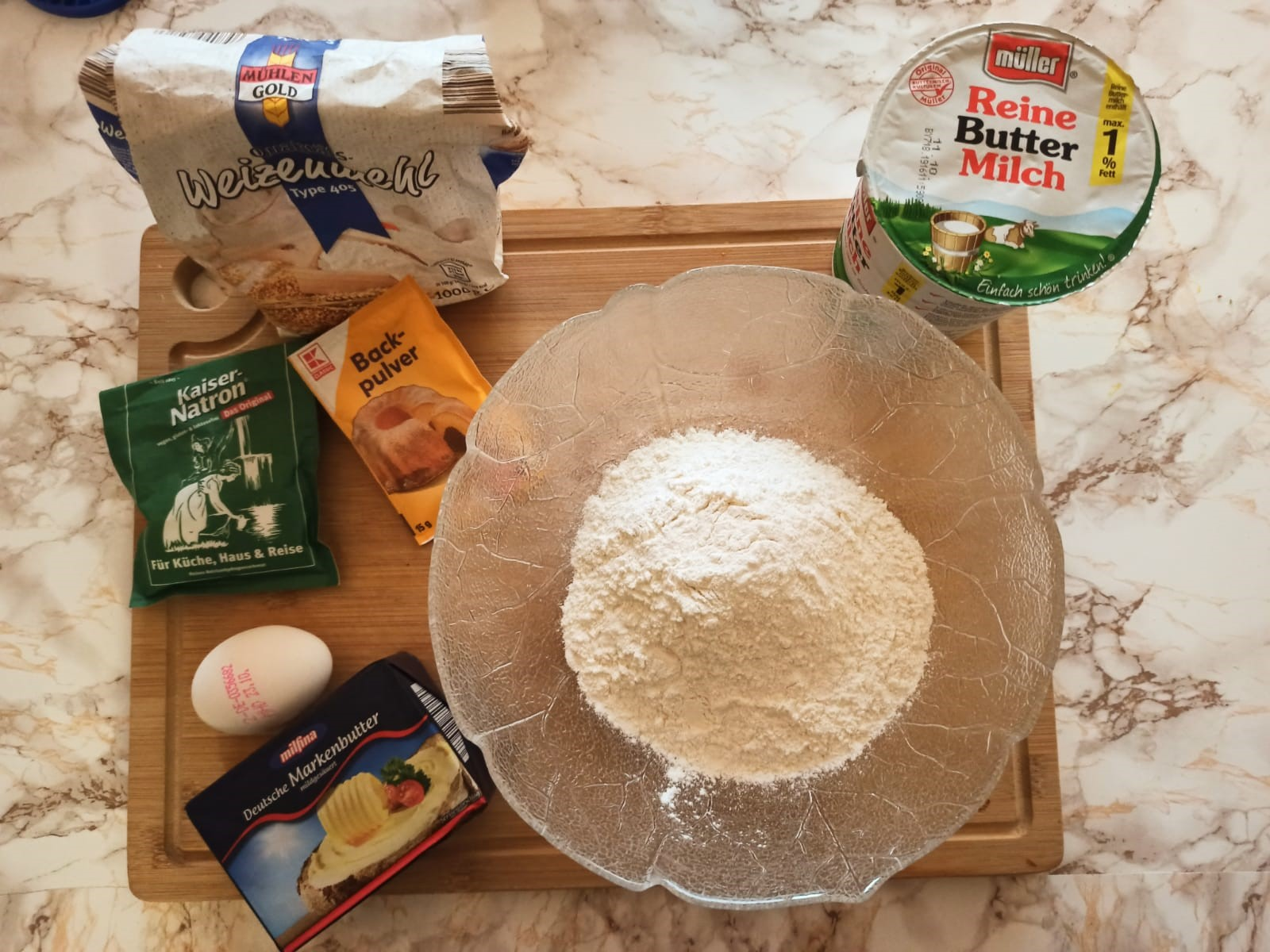 A bowl with flour standing on a table, with other baking ingredients around it.