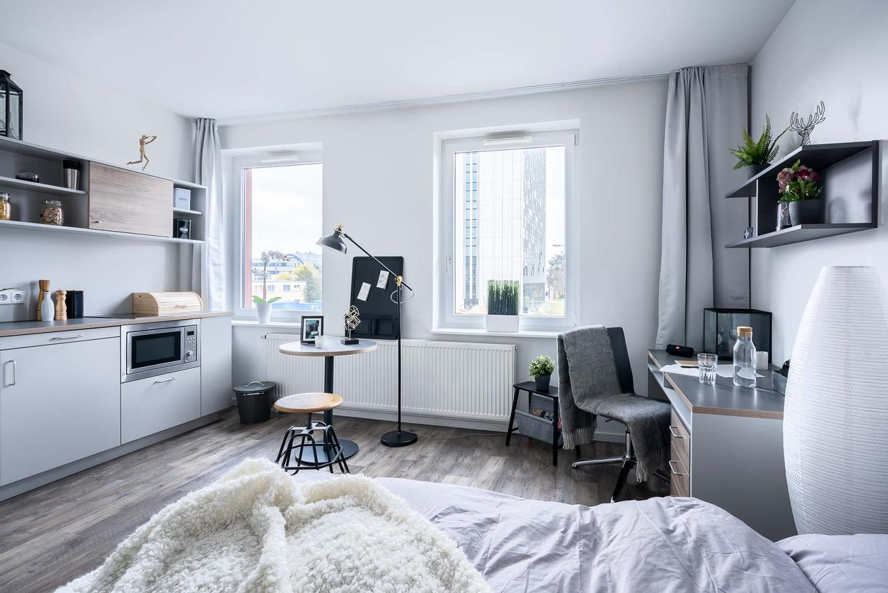A single studio apartment with bed in the front, desk and chair on the right and kitchenette and round eating table to the left. Through the windows, the tower of the Technische Universität of Darmstadt is visible.