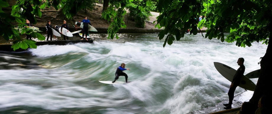 A surfer rides a wave of the Eisbach while other surfers with their boards stand beside, watching him.