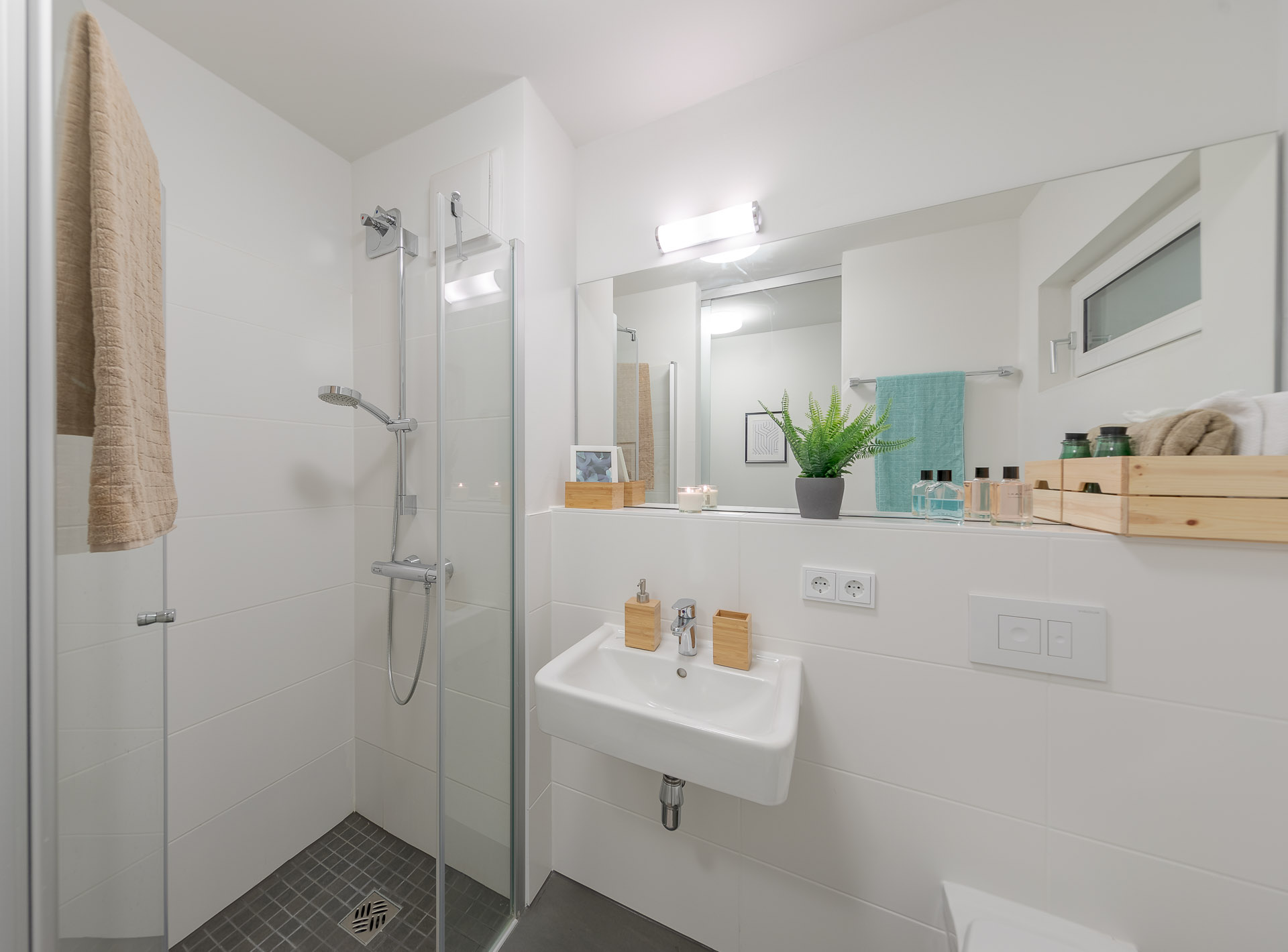 Bathroom view of THE FIZZ Hanover with sink and mirror in the middle, shower room with open glass door to the left and toilet seat barely visible on the bottom right.