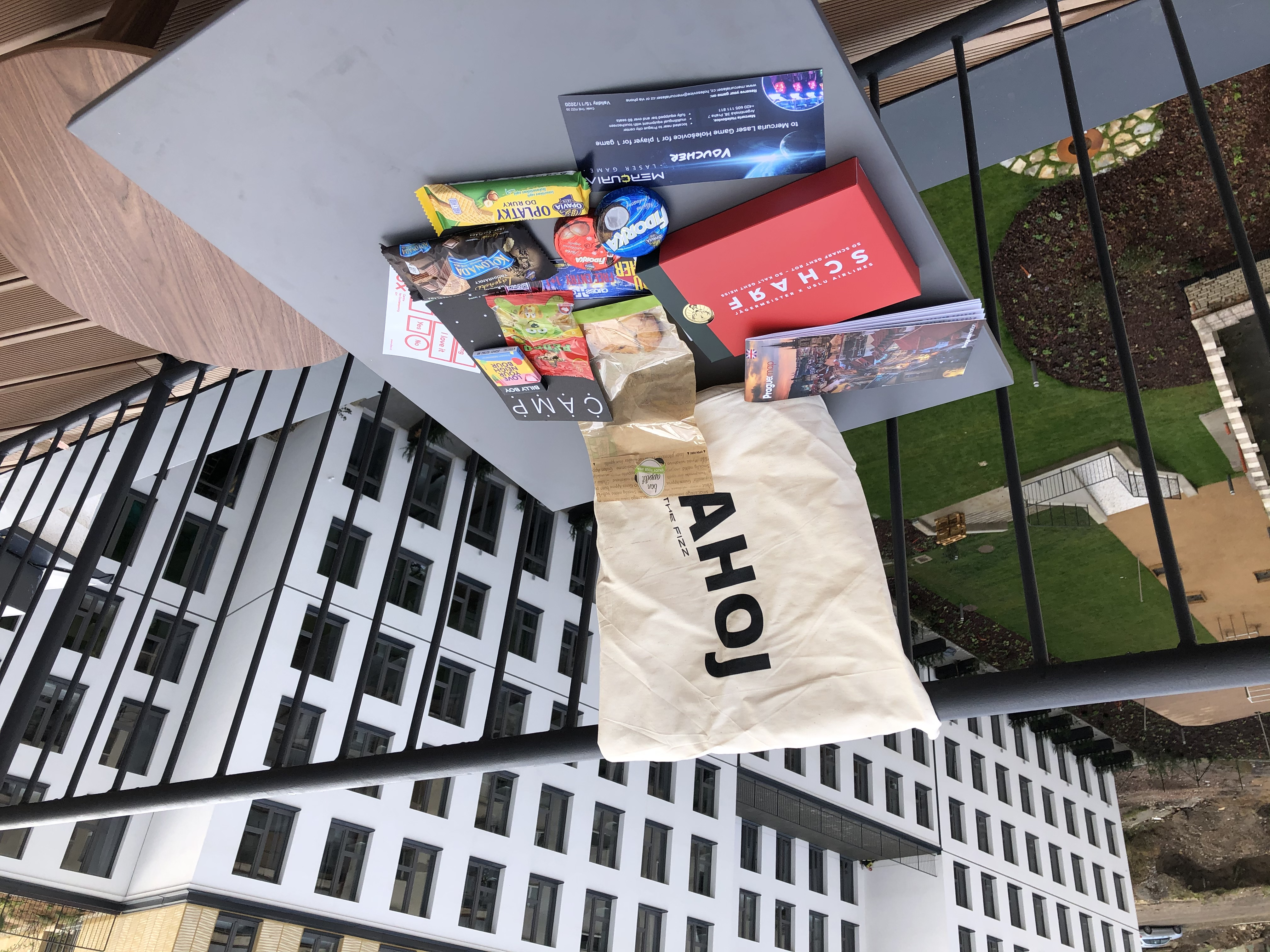 """A square table with sweets - chocolate, cookies, traditional Czech """"oplatky"""" -, vouchers and a THE FIZZ welcome bag with """"AHOJ"""" written on it."""