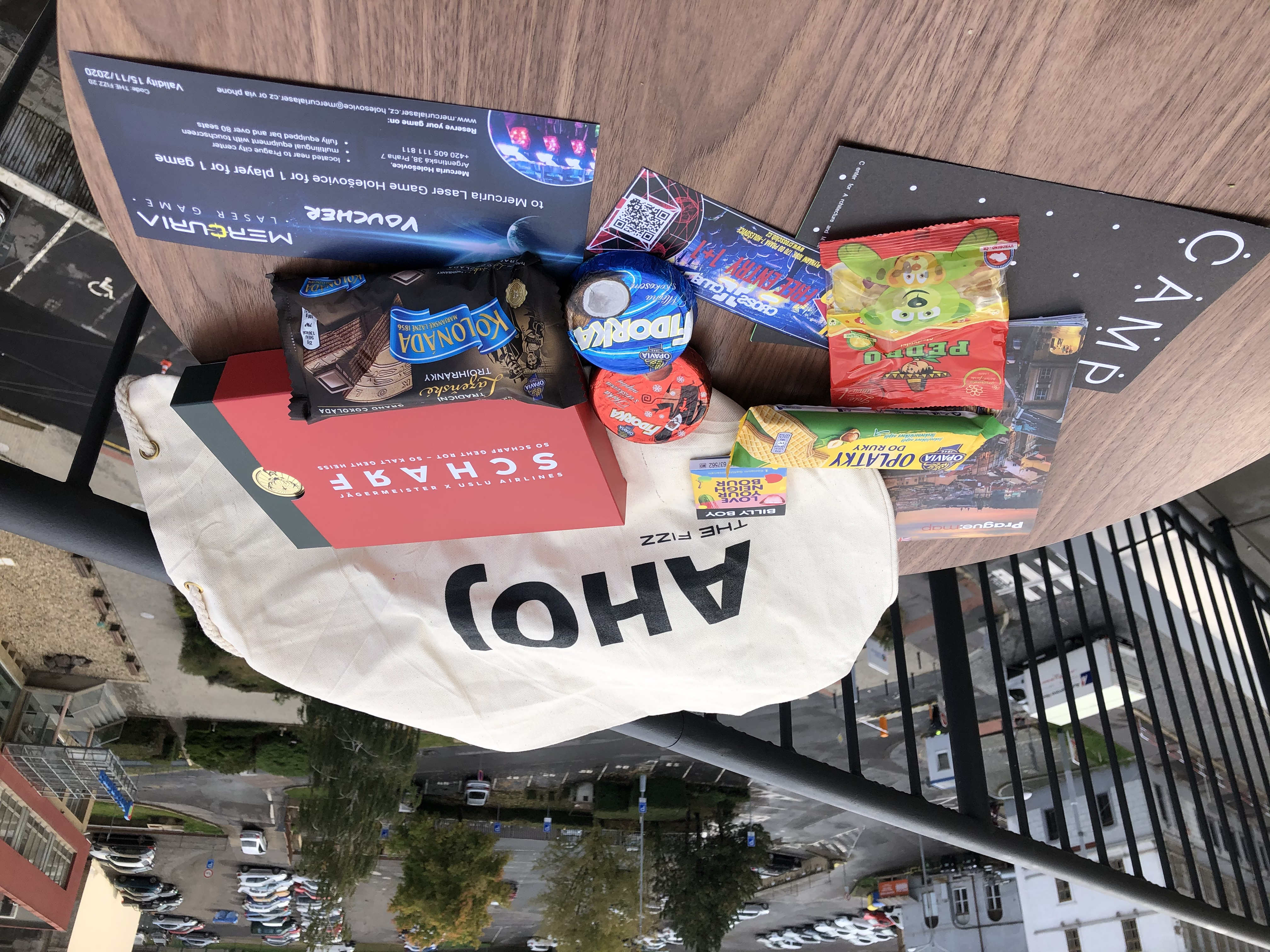 """A round table with sweets - chocolate, cookies, traditional Czech """"oplatky"""" -, vouchers and a THE FIZZ welcome bag with """"AHOJ"""" written on it."""