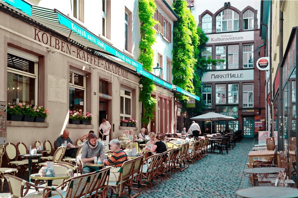 A cozy courtyard in Freiburg with rows of coffee tables where people are sitting.