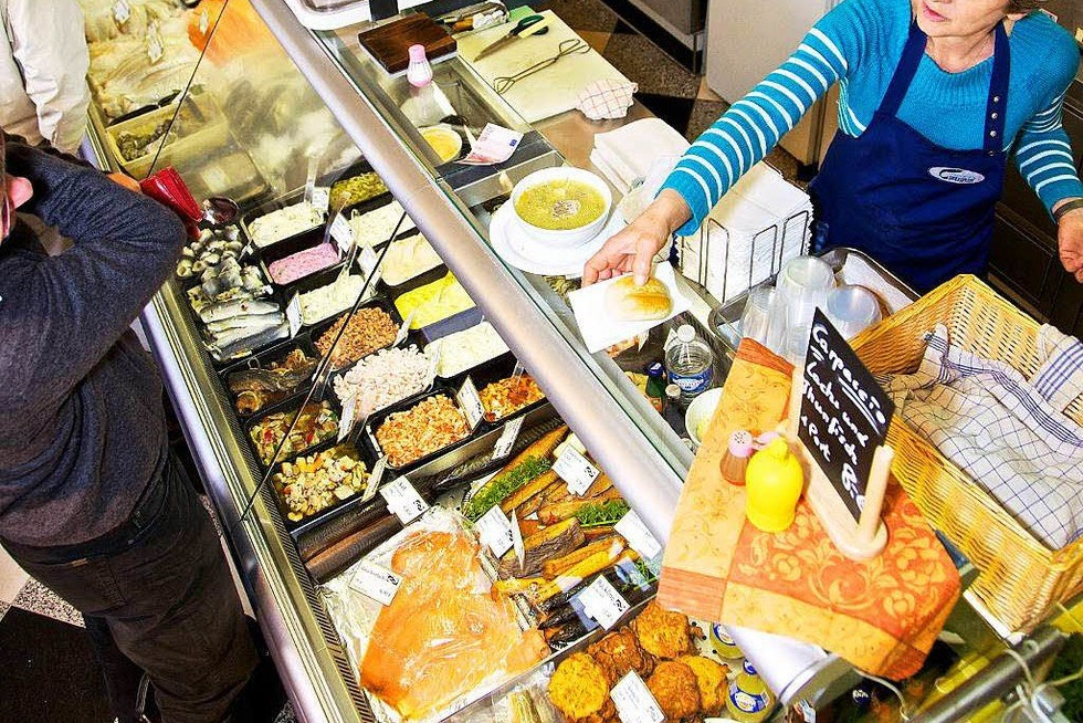 A woman is handing a meal over the top of a display with dips, sauces, fresh and smoked fish and other food.