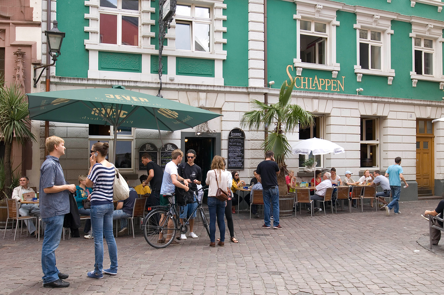 People standing or walking on a street with cobblestones in front of a café.