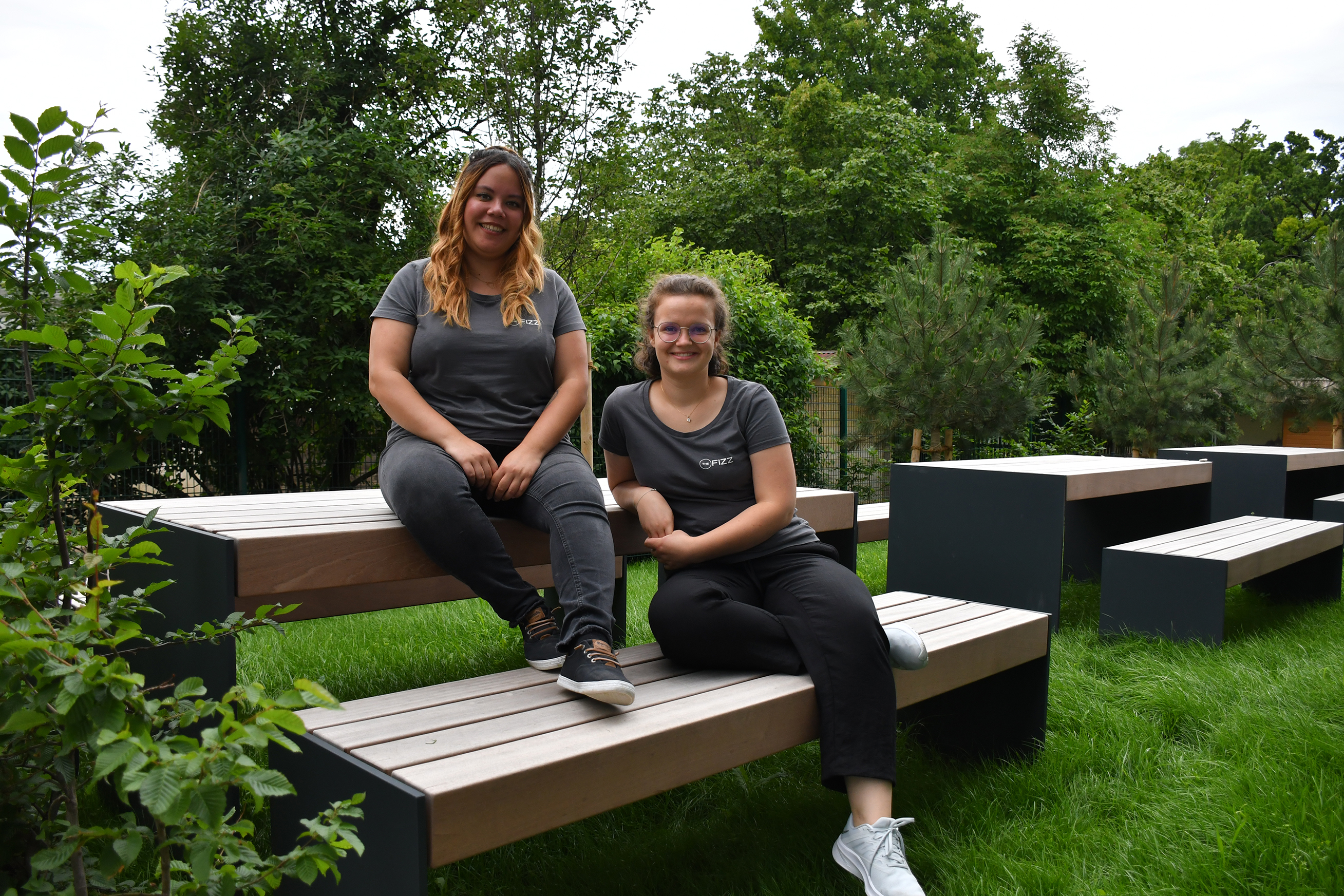 Two girls are sitting casually on a bench outside, surrounded by trees and green. They wear dark grey t-shirts, pants and sneakers. They look directly into the camera, smiling.