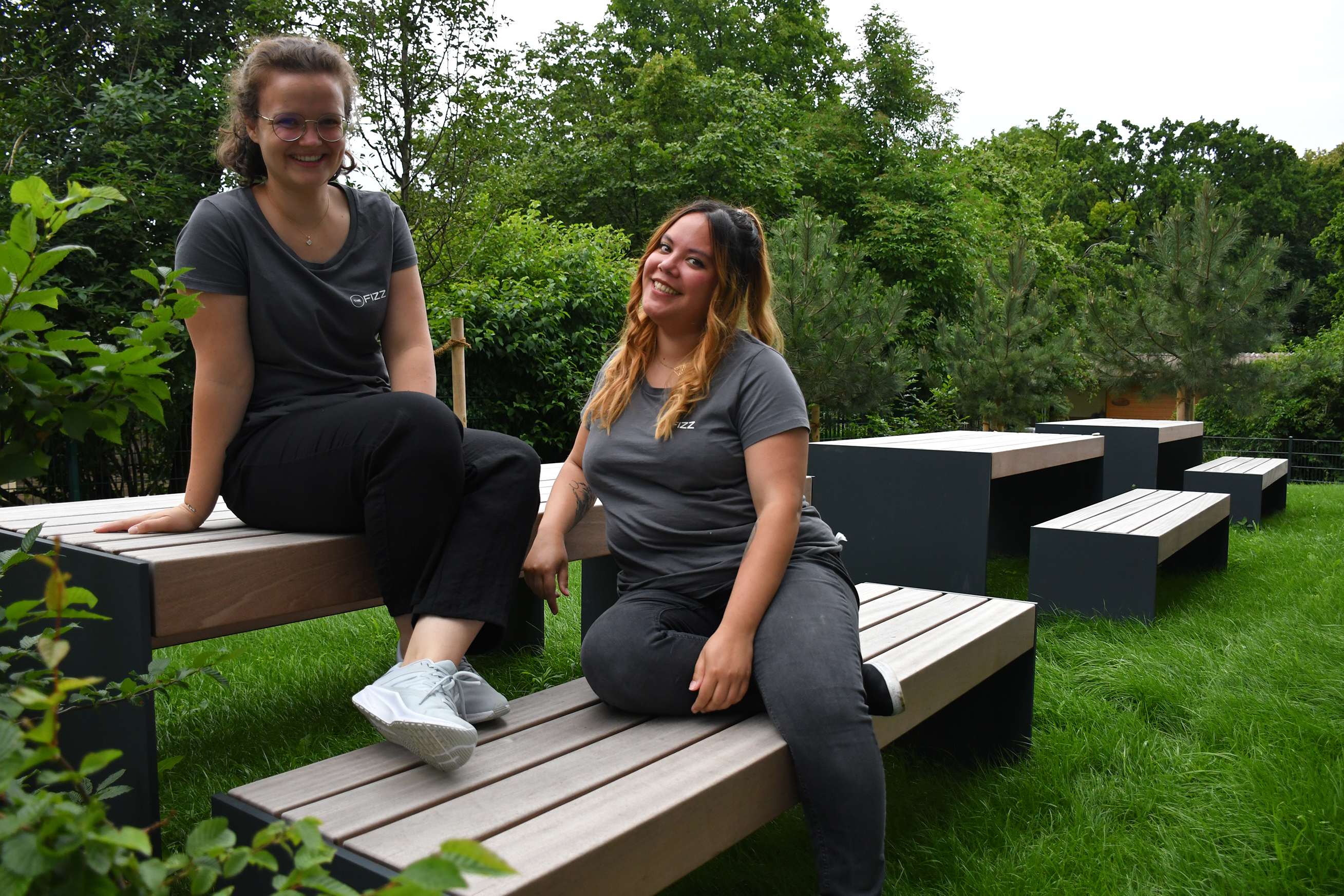 Two girls are sitting casually on a bench outside, surrounded by trees and green. One girl is sitting on the table, the other  on the bench beside. They both look into the camera, smiling.
