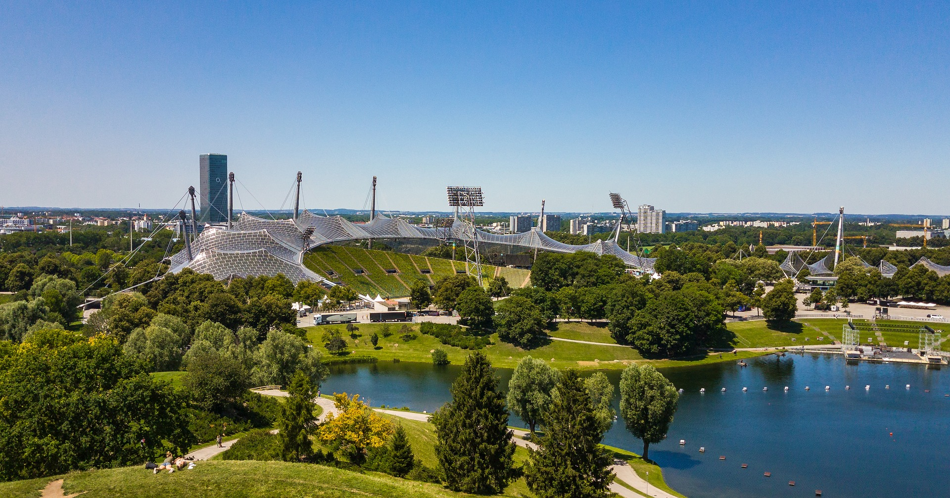 A view of the Olympiapark in Munich on a sunny day, with a deep blue lake in front, lots of green trees and blue sky.