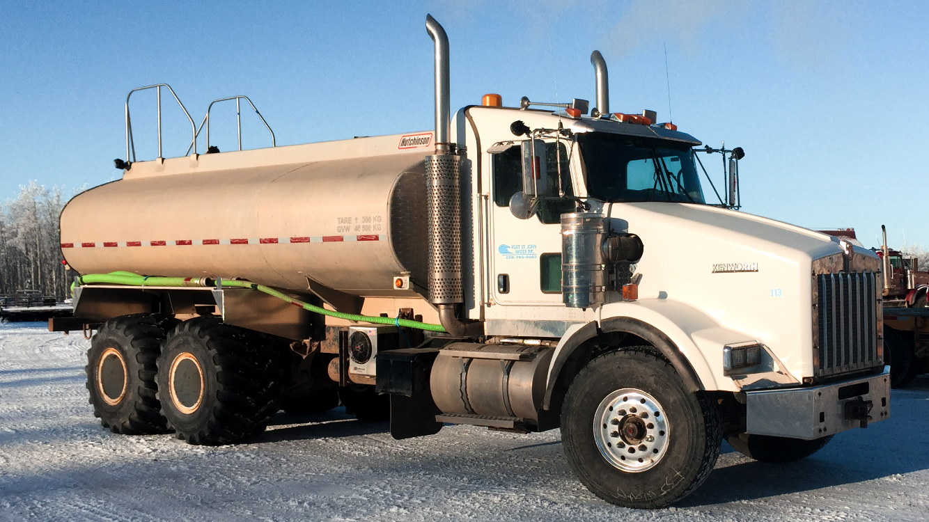 Truck with spray bar and floater tires for ice road construction