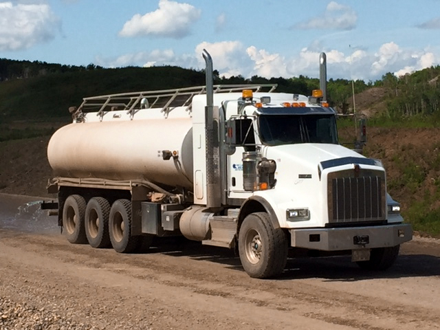Truck with spray bar for dust control and road construction