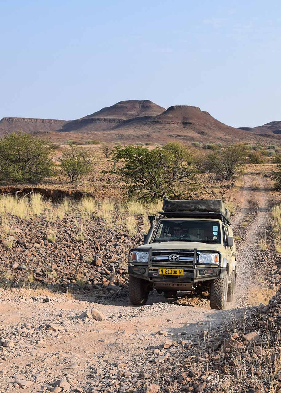 A Safari Drive Land Cruiser climbing a rocky outcrop in the Namibian desert