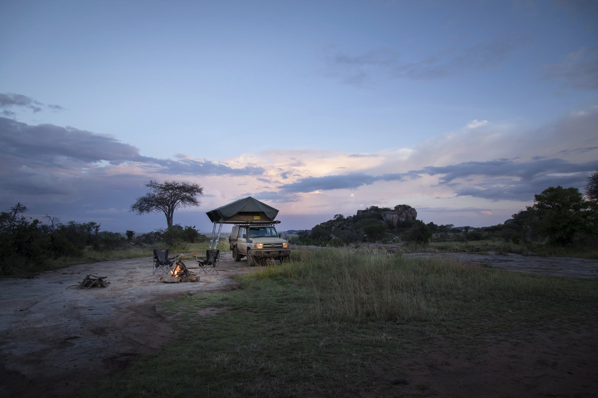 Safari Drive Land Cruiser with rooft tent and campfire in Botswana after sunset