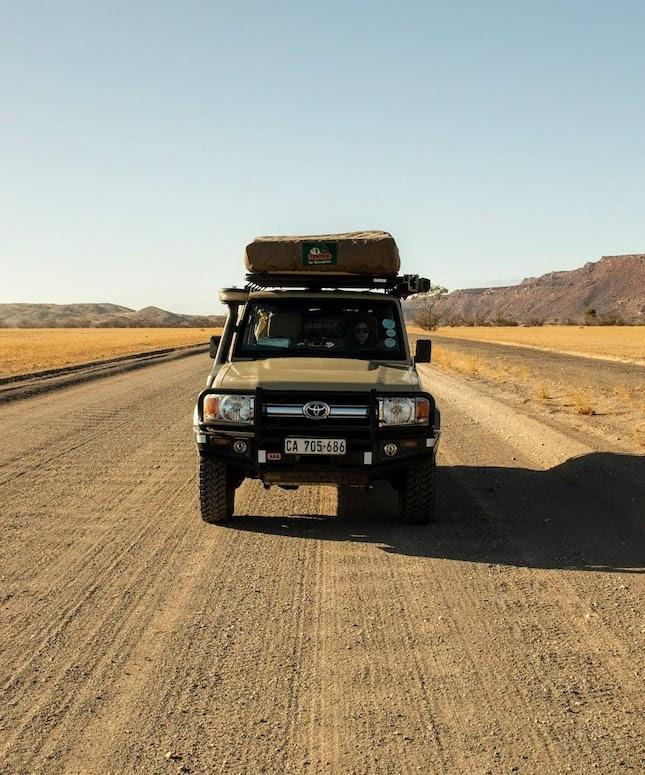 A front view closeup of a Safari Drive Land Cruiser on a dirt track road in Namibia
