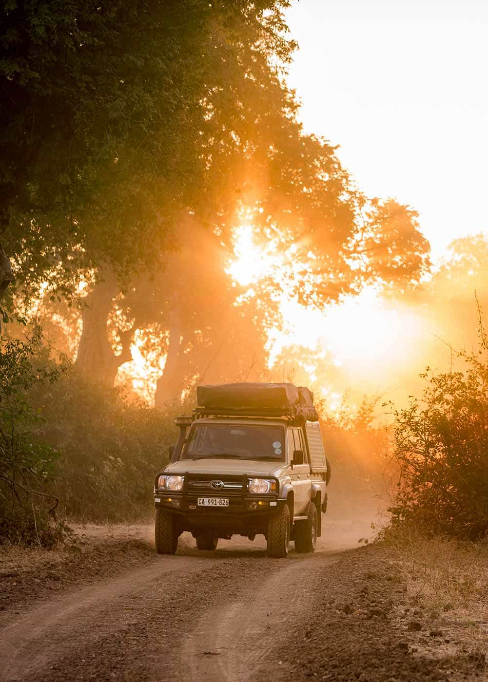 Safari Drive Vehicle driving on African dirt road at sunset