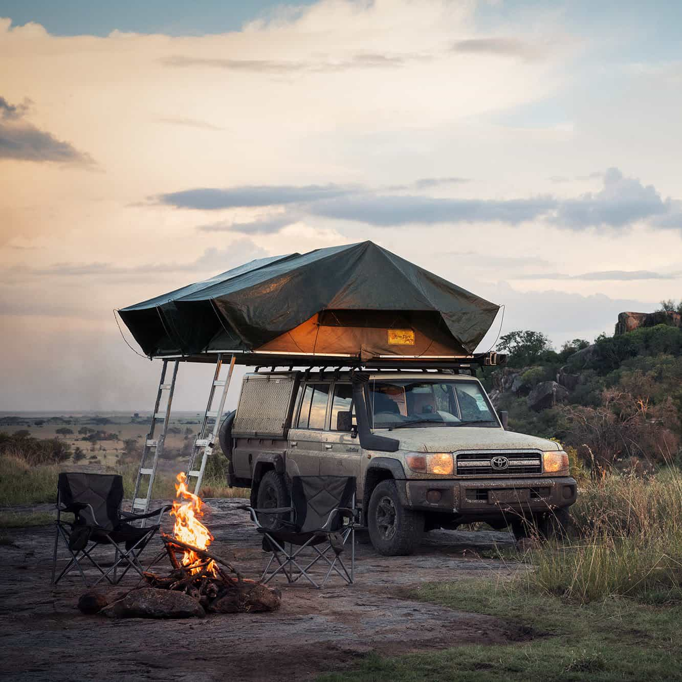 Safari Drive Land Cruiser with roof tent and camp set up at dusk
