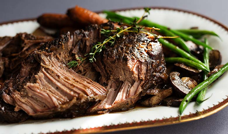 Slow cooked beef cut with vegetables and herbs
