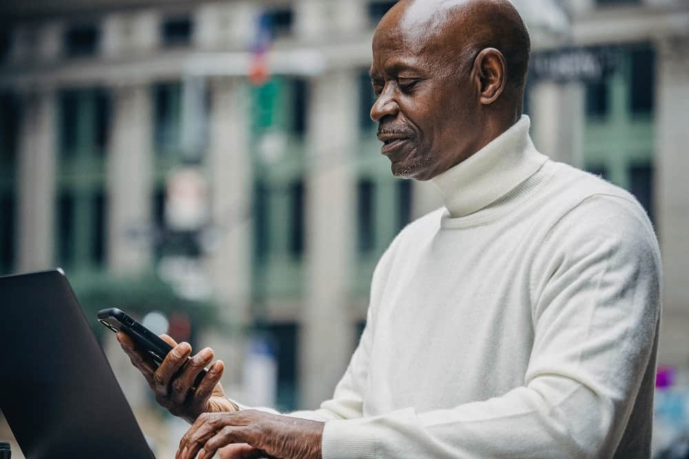 Older man shopping on his phone and laptop