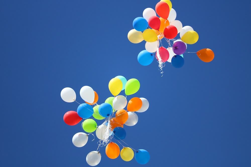 A photo of birthday balloons floating into the sky