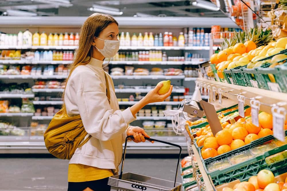 A woman picking fruit from the aisle of a supermarket