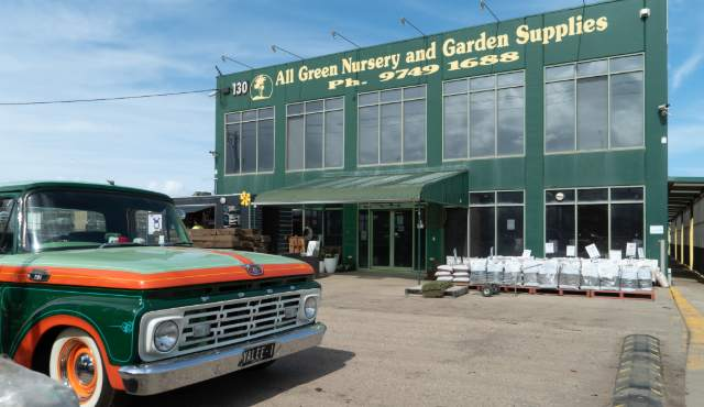 All Green nursery store front with car