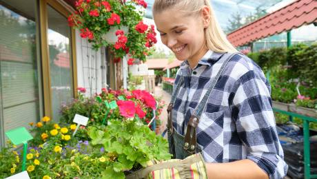 garden centre worker smiling whilst tending to nursery flowers