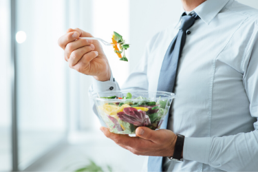 person in formal attire eating a salad standing up