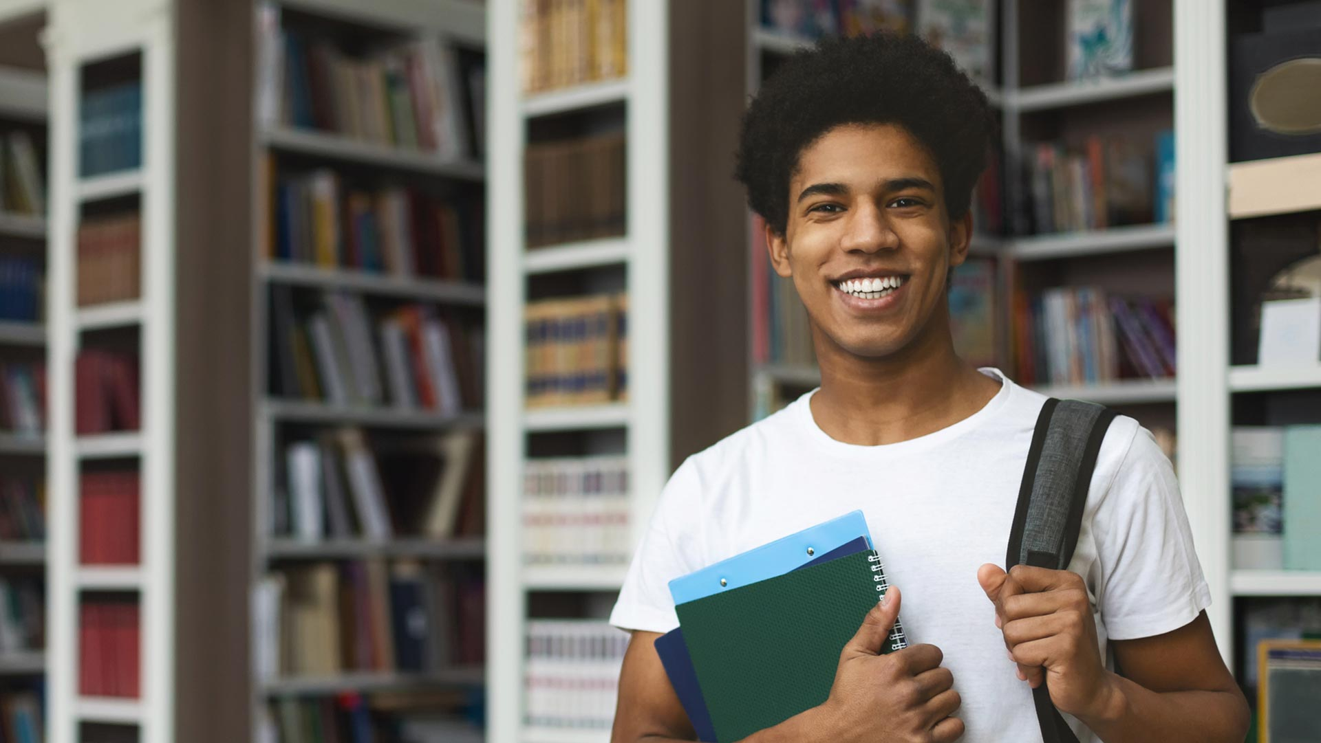 A young black man smiles in his high school library