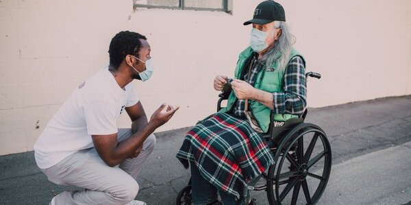 A student helping an elderly person in a wheelchair