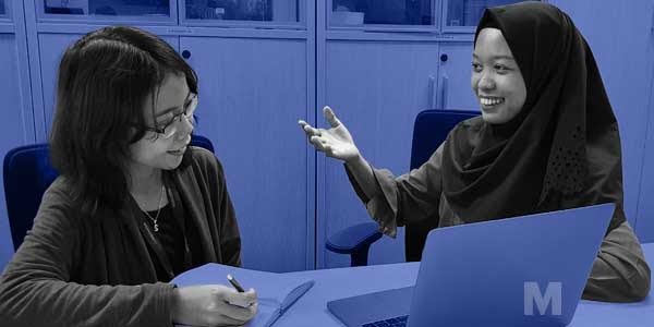Stylised photo of two Asian students studying together.