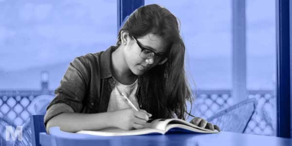 Stylised photo of an aspiring medical student writing in a notebook with a pen.