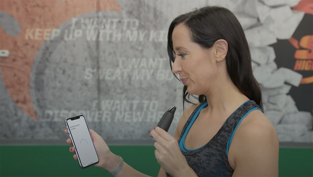 image of woman taking a breath with her lumen metabolism tracker connected to the iphone mobile app at the gym