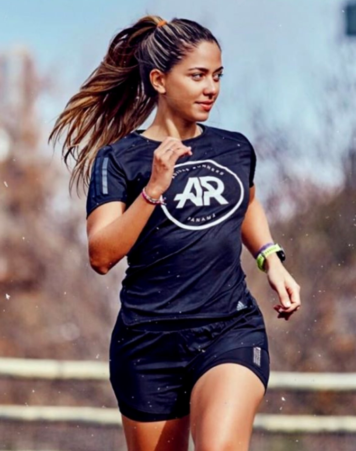Young woman running in Adidas Run Club black shirt
