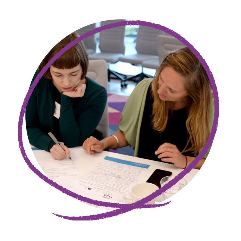 Photo of two women who work at People with Disability Australia: Meg and Kate sitting at desk. Meg is writing on a piece of paper and Kate is looking down at the paper.
