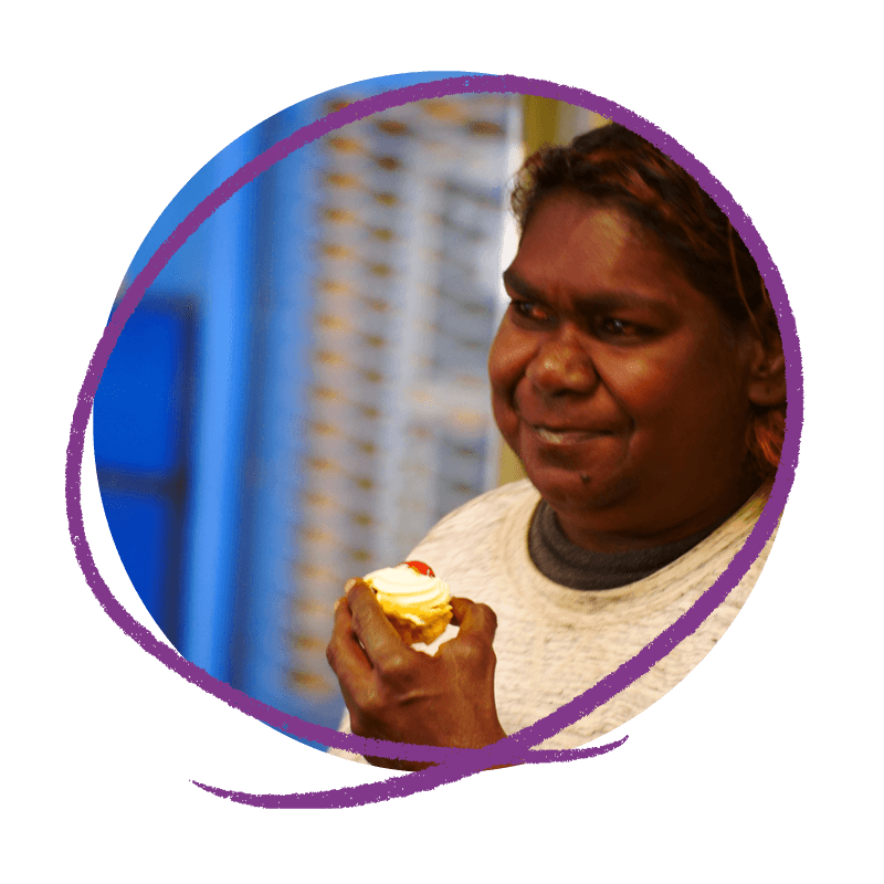 Photo of an Aboriginal woman holding a biscuit.