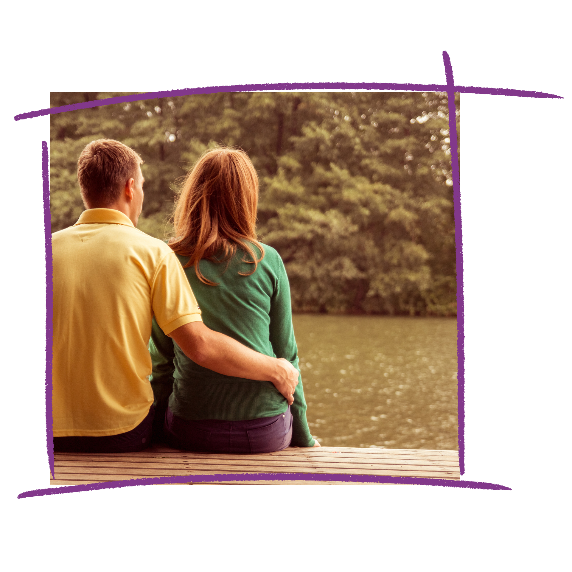 Photo of a man and a woman sitting on a wooden bench looking out at the water. The man has his arm around the woman.