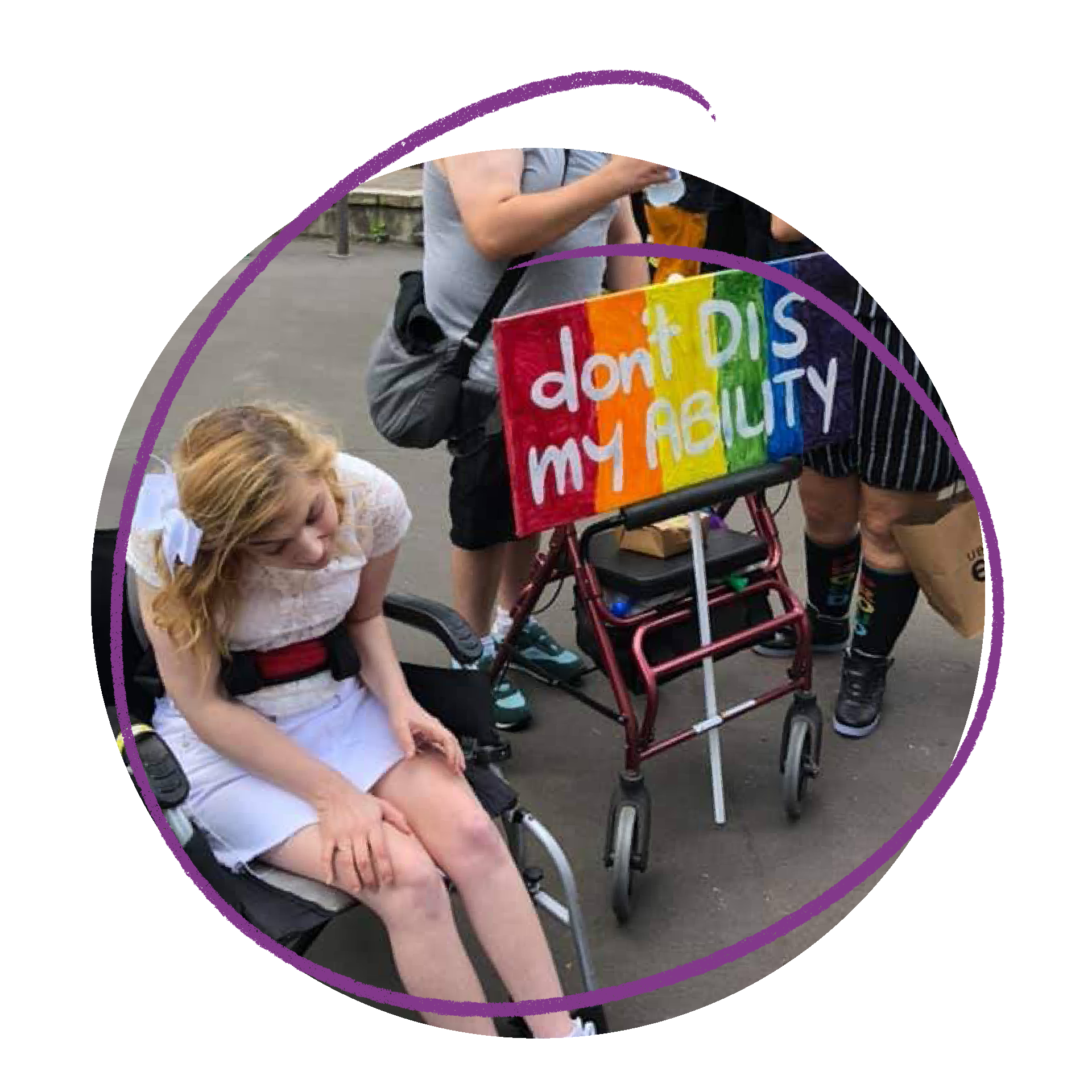 Phto of a young woman at the Mardi Gras. She is using a wheelchair and wearing a white dress. There is a person with a rainbow sign that says 'Don't DIS my ability' behind her.