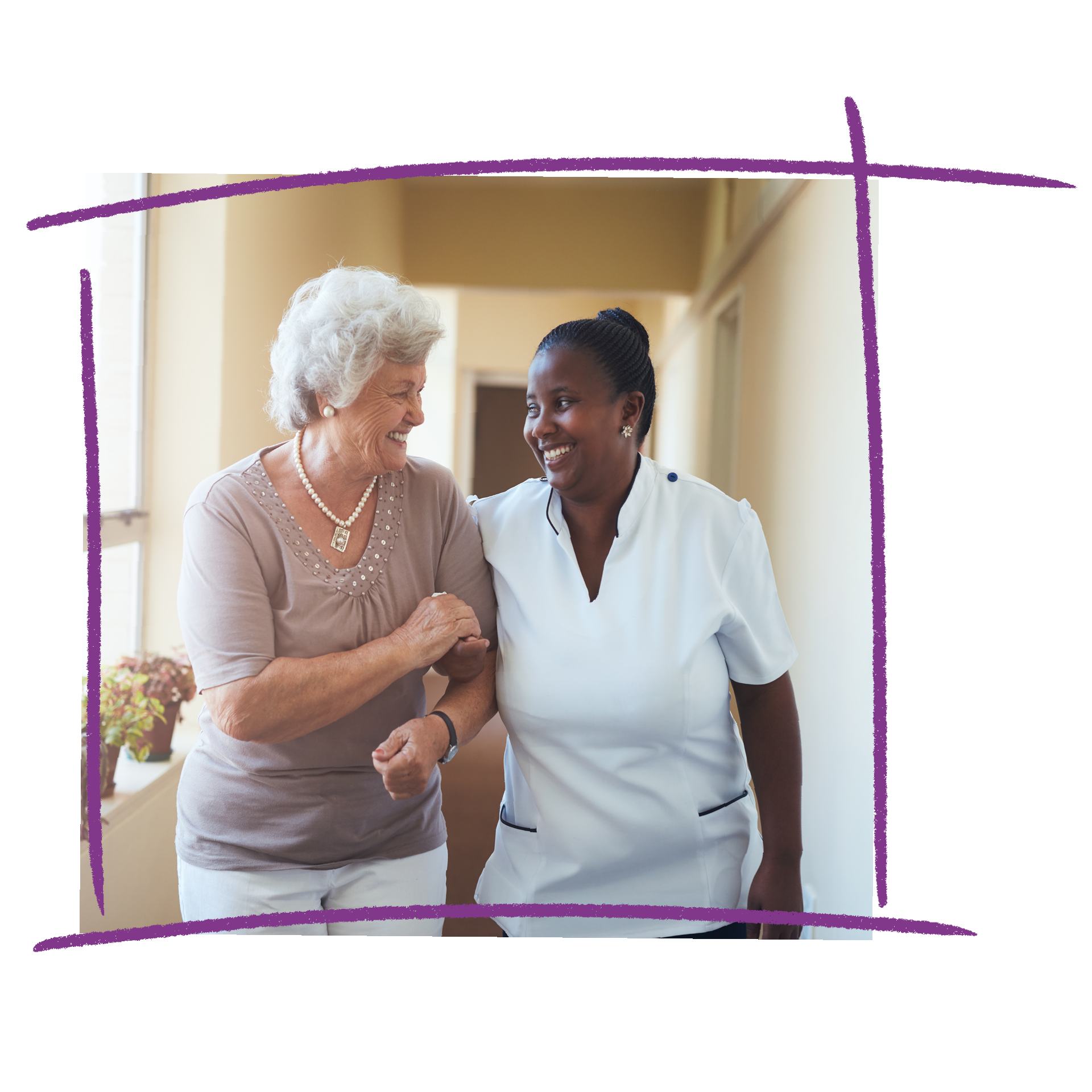 Photo of an older woman linking arms with a nurse wearing a white uniform. They are walking down a hallway together.