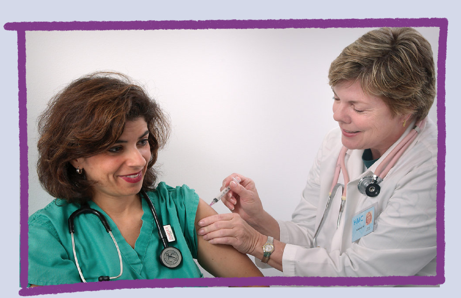 Photo of a doctor giving an injection to a nurse.