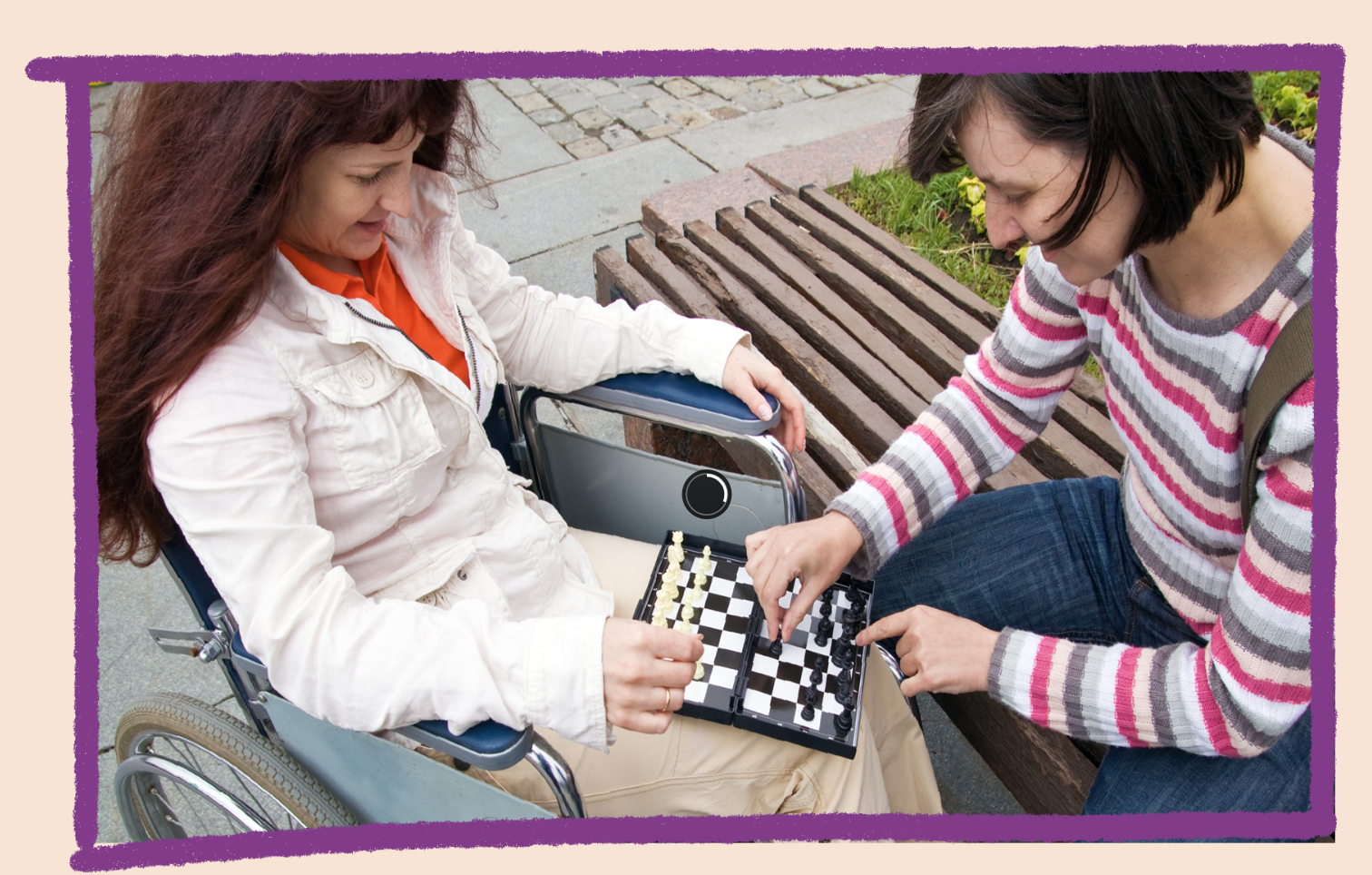 Photo of two women playing chess in a park. One is in a wheelchair and the other is sitting on a park bench.