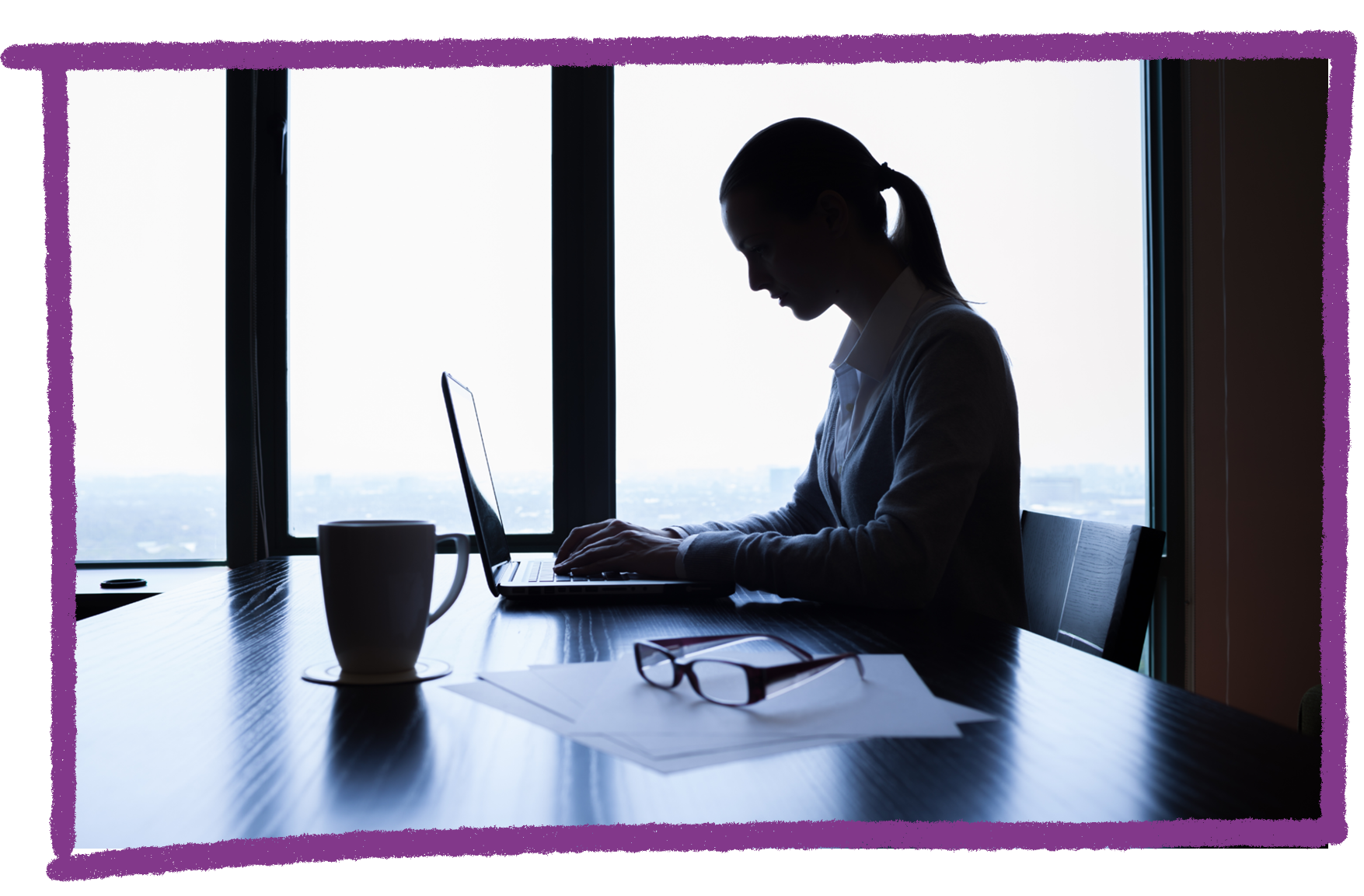 A photo of a woman on a computer in a dark office