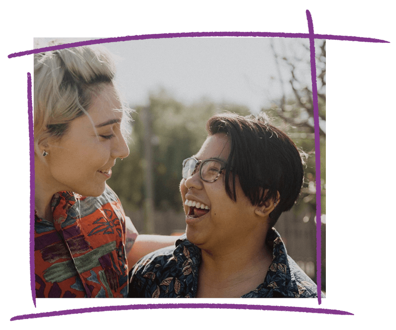 A photo of Kirra (non-binary person) and their partner smiling