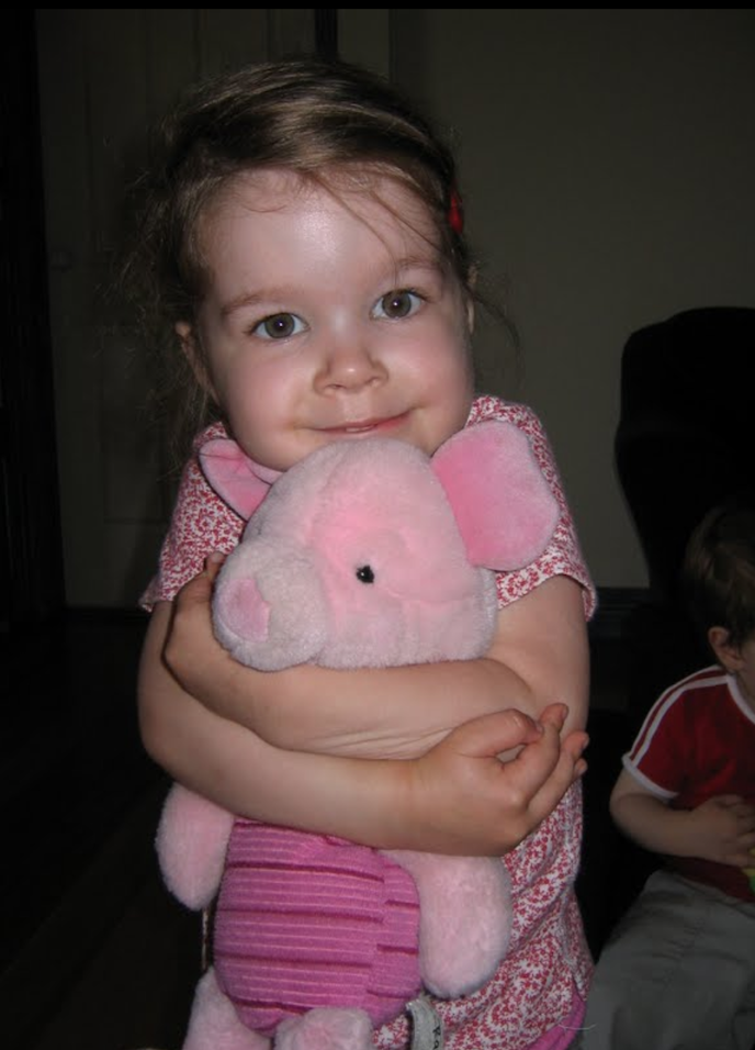 Photo of young Issy holding a pink pig plush toy.