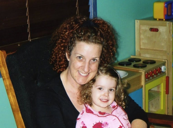 Photo of young Issy sitting on her mum's lap.