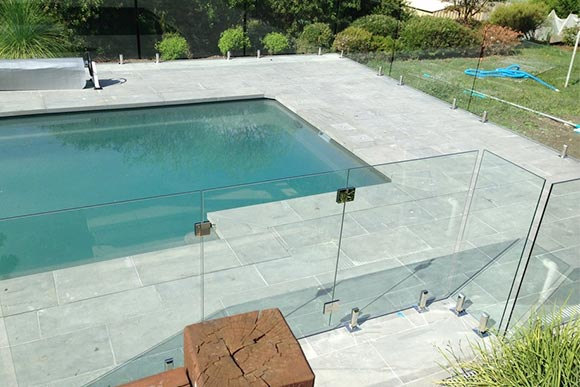 Outdoor patio with frameless glass fencing around pool